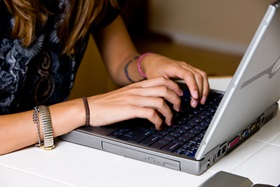 girls hands typing on laptop